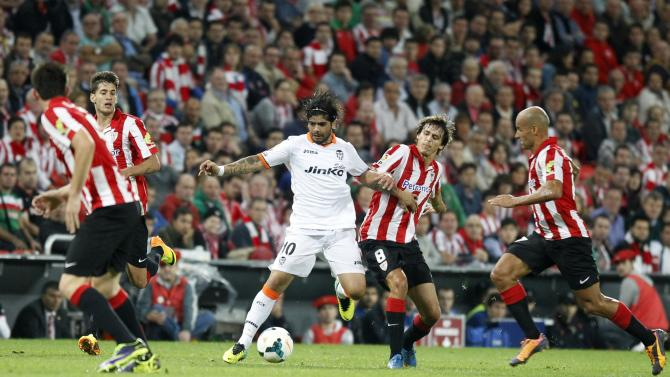 Valencia's Banega challenges Athletic Bilbao's Iturraspe during their Spanish first division soccer match in Bilbao