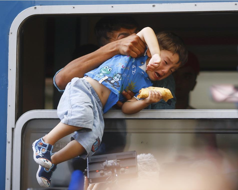 A migrant pulls a boy inside a train through a window at the Keleti train station in Budapest