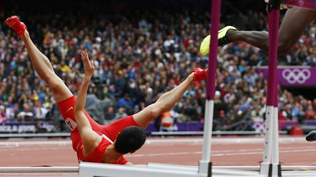 China's Liu Xiang falls onto the track during his men's 110m hurdles round 1 heat at the London 2012 Olympic Games at the Olympic Stadium (Reuters)