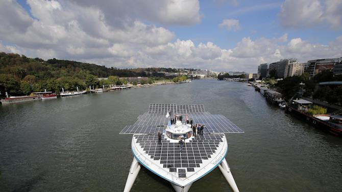 The Turanor PlanetSolar, the world's largest solar boat, travels on the Seine river in Sevres, outside Paris, Tuesday, Sept. 10, 2013. The PlanetSolar with its 537 square meters of photovoltaic panels powering 6 blocks of lithium-ion batteries, accomplished the first around the world trip powered only by solar energy in May 2012. (AP Photo/Christophe Ena)
