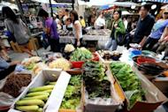 People walk past a vegetable stall in Namdaemun market in Seoul. South Korea's inflation rate was the lowest for more than 12 years in August, official figures showed Monday, raising prospects of an imminent interest rate cut