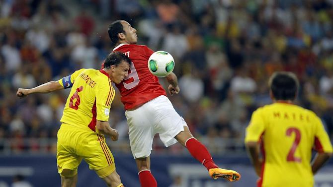 Turkey's Umut Bulut, right, jumps for a header the ball with Romania's Vlad Chiriches during a World Cup Group D qualifying soccer match between Romania and Turkey at the National Arena stadium in Bucharest, Romania, Tuesday, Sept. 10, 2013