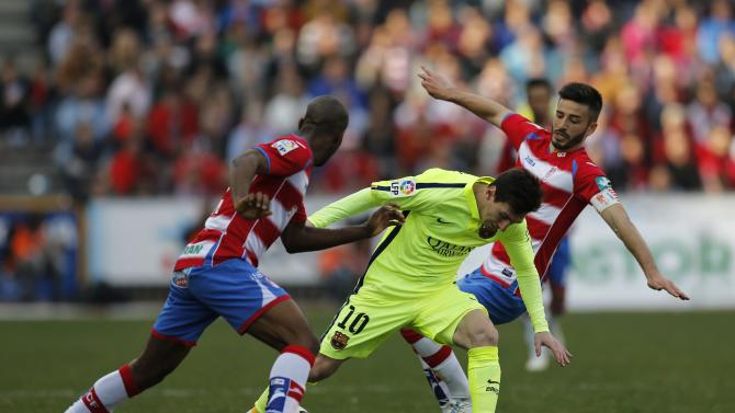 Barcelona's Messi is challenged by Granada's Foulquier and Riki during their Spanish first division soccer match in Granada