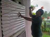 A resident nails a sheet of corrugated metal onto the shutters to his house in Suva, Fiji, on December 17, 2012. Despite the damage, officials said there were no reported fatalities as the storm headed out to sea early Tuesday