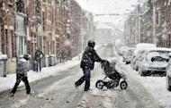 A woman crosses a snow-covered street with a pushchair in Armentieres, northern France, on March 5. An increase in energy imports due to a cold snap in February sent France's trade deficit jumping by nearly 15 percent in February to hit 6.4 billion euros ($8.4 billion), customs data showed Friday