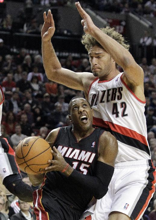 Miami Heat guard Mario Chalmers, left, drives against Portland Trail Blazers center Robin Lopez during the first half of an NBA basketball game in Portland, Ore., Saturday, Dec. 28, 2013