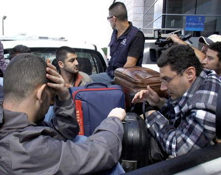 Syrian men sit in the bed of a truck after being detained at Toncontin international airport in Tegucigalpa