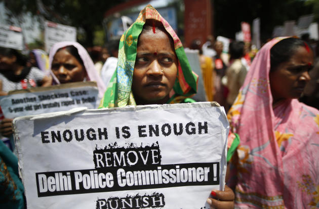 An Indian woman holds a poster as she protests with others against how Indian authorities handle sex crimes near the Parliament in New Delhi, India, Monday, April 22, 2013 after a second suspect was a