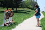 A woman stands with her head bowed after laying flowers at a makeshift memorial near the Sikh Temple of Wisconsin in the city of Oak Creek. The small US community struggled to understand Tuesday how a racist former soldier with links to white supremacists acted on his hatred and shot dead six unarmed people at a suburban Sikh temple