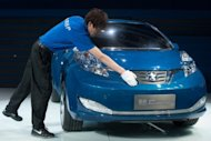 A man cleans a concept electric car by joint Nissan-Dongfeng company 'Venucia', at the Auto China 2012 car show in Beijing. Foreign carmakers in China say Beijing is pressuring them to produce dedicated new brands so their local partners can gain technical know-how, but experts warn the strategy could backfire