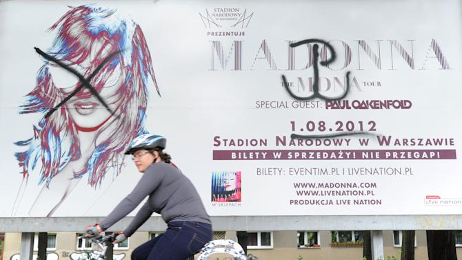 A cyclist rides past a defaced Madonna concert billboard in Warsaw, Poland, Wednesday, July 18, 2012.  Organizers of the concert have agreed to a request from city officials to start the show with a minute of silence and a brief clip about the 1944 revolt against Nazi rule, the Warsaw Uprising, in a nod to war veterans. Some veterans and young Catholics have voiced anger that the Aug. 1 concert falls on the 68th anniversary of the uprising, a day marked with a somber tone. The sign on the right of the billboard is the symbol of Poland's fight against the Nazis. (AP Photo/Alik Keplicz)