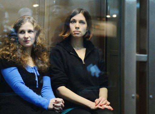 "The two jailed members of the all-girl punk band ""Pussy Riot,"" Maria Alyokhina (L) and Nadezhda Tolokonnikova (R), sit in a glass-walled cage in a court in Moscow in October 2012. Alyokhina and Tolokonnikova have fired their high-profile legal team and hired the lawyer who helped free their bandmate, the husband of one of the women told AFP on Monday."