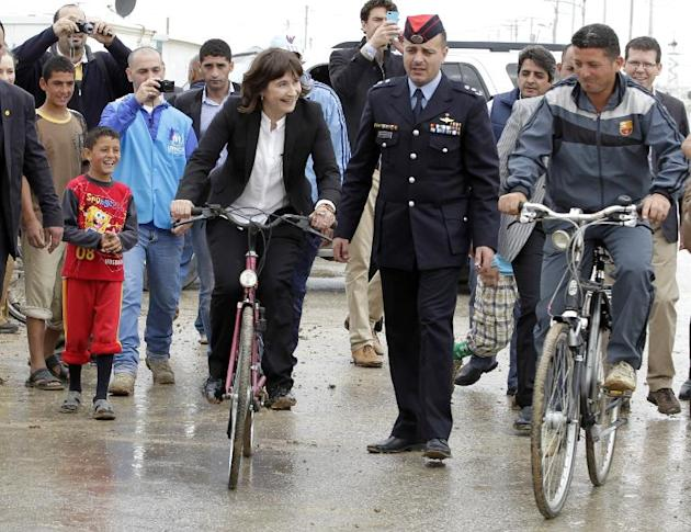 Netherlands' Minister of Foreign Trade and Development Cooperation, Lilianne Ploumen (L), rides a bicycle at the UN-run Zaatari refugee camp, north east of the Jordanian capital Amman, on March 29