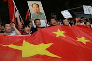 Demonstrators carry a Chinese flag during an anti-Japanese protest over the Diaoyu islands issue, known as the Senkaku islands in Japanese, outside the Japanese Embassy in Beijing on September 15. A swathe of Japan's biggest corporate names padlocked factories in China as violent anti-Japan protests sparked safety fears, and threatened economic ties worth more than $300 billion a year