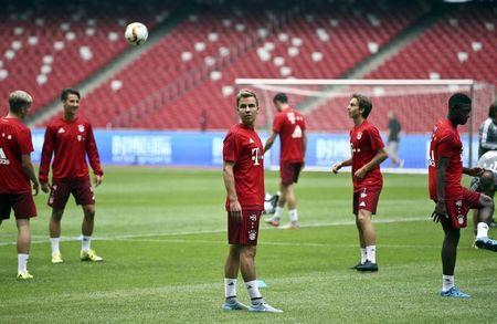 Bayern Munich's Goetze looks at a ball next to teammates during a training session ahead of a friendly soccer match against Valencia, at the National Stadium, also known as the Birds' Nest, in Beijing