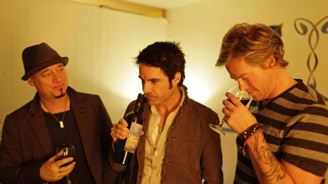In this photo taken Wednesday April 11, 2012, from left, Jimmy Stafford, Patrick Monahan, and Scott Underwood of the band Train sample some of their wine before their concert at the Great American Music Hall in San Francisco. (AP Photo/Eric Risberg)
