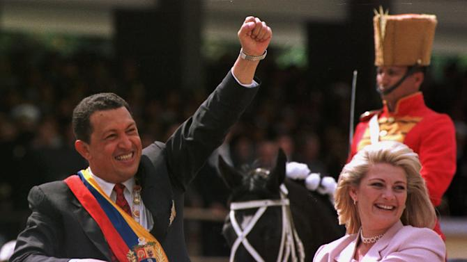 In this Feb. 4, 1999 file photo, Venezuela's newly sworn in President Hugo Chavez salutes the crowd next to his wife Marisabel Chavez during a military parade commemorating the seventh anniversary of his failed 1992 coup in Caracas, Venezuela.  Venezuela's Vice President Nicolas Maduro announced on Tuesday, March 5, 2013 that Chavez has died.  Chavez, 58, was first diagnosed with cancer in June 2011.  (AP Photo/Douglas Engle, File)