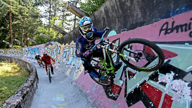 Downhill bikers Mulic, Hadzic and Kolar train on the disused bobsled track from the 1984 Sarajevo Winter Olympics on Trebevic mountain near Sarajevo