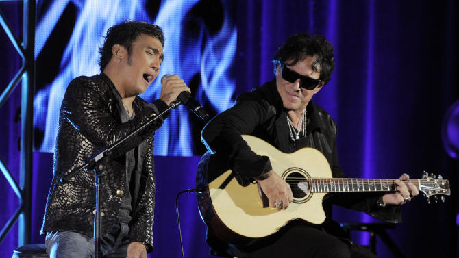 "Arnel Pineda, left, and Neal Schon of the rock band Journey perform onstage following a panel discussion on the Independent Lens documentary ""Don't Stop Believin': Everyman's Journey,"" at the PBS Summer 2013 TCA press tour at the Beverly Hilton Hotel on Tuesday, August 6, 2013 in Beverly Hills, Calif. (Photo by Chris Pizzello/Invision/AP)"