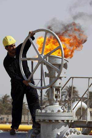FILE - In this file photo of Friday, July 17, 2009, an Iraqi worker operates valves at the Nahran Omar oil refinery in Zubair near the city of Basra, 340 miles (550 kilometers) southeast of Baghdad, Iraq. The turmoil in Iraq has thrown the OPEC member's ambitious plans to boost oil production into doubt, threatening to crimp its most vital economic lifeline. Northern oil fields imperiled by the militants' advance have been shut down, and companies have begun evacuating workers elsewhere in the country. Iraq's Kurdish minority has moved to solidify control over the northern oil-rich city of Kirkuk and other disputed areas, weakening Baghdad's claims to the energy riches buried beneath while bolstering the Kurds' aspirations of greater autonomy. (AP Photo/Nabil al-Jurani, File)