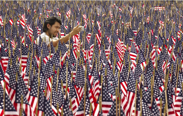 Edgar Yepez takes a photo among 7,000 American flags on display outside the Long Center in Austin, Texas, on Memorial Day, Monday, May 27, 2013. The flags are in honor of the fallen veterans of the wa