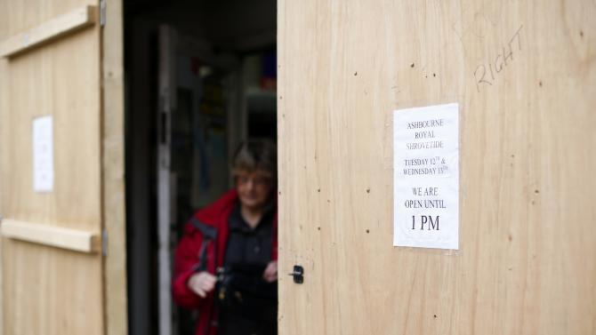 A woman leaves a boarded-up shop before the annual Shrovetide football match in Ashbourne