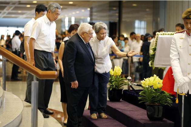 Former U.S. Secretary of State Henry Kissinger, center, is accompanied by Ho Ching, right, wife of Singapore's Prime Minister Lee Hsien Loong, second left, as he pays his respects  to the late Lee