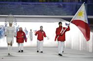 Michael Christian Martinez of the Philippines carries the national flag as he leads his team during the opening ceremony of the 2014 Winter Olympics in Sochi, Russia, Friday, Feb. 7, 2014. (AP Photo/Mark Humphrey)