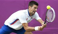Serbia's Novak Djokovic returns a shot to Australia's Lleyton Hewitt in the third round men's singles tennis match at the 2012 London Olympic Games at the All England Tennis Club in Wimbledon, southwest London. Djokovic won the match