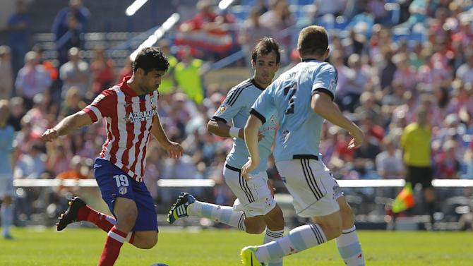 Atletico de Madrid's Diego Costa from Brazil, left, in action with Celta de Vigo's Andreu Fontas, right, Borja Oubina second left, as during a Spanish La Liga soccer match at the Vicente Calderon stadium in Madrid, Spain, Sunday, Oct. 6, 2013