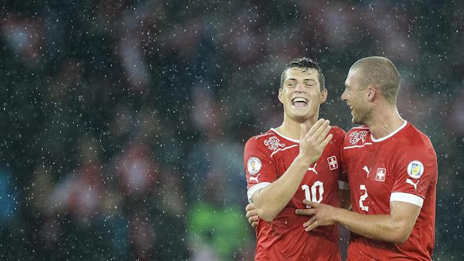 Switzerland's Granit Xhaka, left, and Switzerland's Pajtim Kasami, right, celebrate after winning the FIFA World Cup 2014 group E qualifying soccer match between Switzerland and Slovenia at the Stade de Suisse stadium in Bern, Switzerland, Tuesday, October 15, 2013