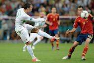 Portugal forward Cristiano Ronaldo (left) kicks the ball towards goal as Spain midfielder Sergio Busquets looks on during the Euro 2012 semi-final at the Donbass Arena in Donetsk, Ukraine