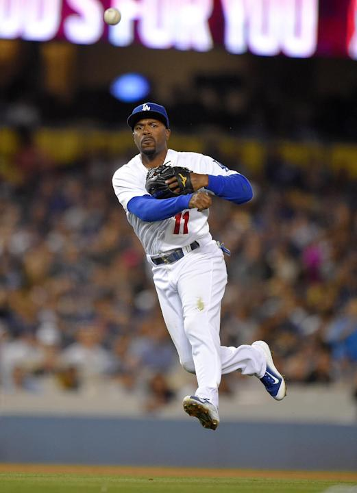 El campocorto Jimmy Rollins, de los Dodgers de Los Angeles, lanza a primera base en su intento por poner fuera a Willie Bloomquist, de los Marineros de Seattle, el martes 14 de abril de 2015, en Los A