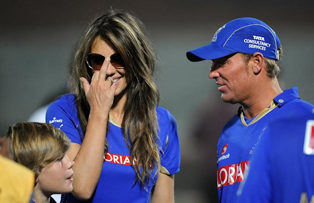 RESTRICTED TO EDITORIAL USE. MOBILE USE WITHIN NEWS PACKAGE Rajasthan Royals captain Shane Warne (L) talks his girlfriend Liz Hurley (C) after victory during the IPL Twenty20 match between Kochi Tuske