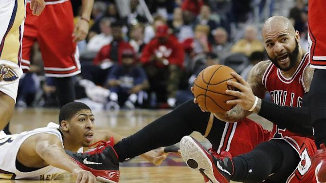 Chicago Bulls forward Carlos Boozer (5) grabs a loose ball in front of New Orleans Pelicans forward Anthony Davis during the second half of an NBA basketball game in New Orleans, Saturday, Feb. 1, 2014. The Pelicans defeated the Bulls 88-79