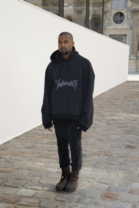 Kanye West poses as he arrives at Christian Dior's fall-winter 2015-2016 fashion collection, as part of Paris Fashion Week, presented in Paris, France, Friday, March 6, 2015. (AP Photo/Thibault Ca