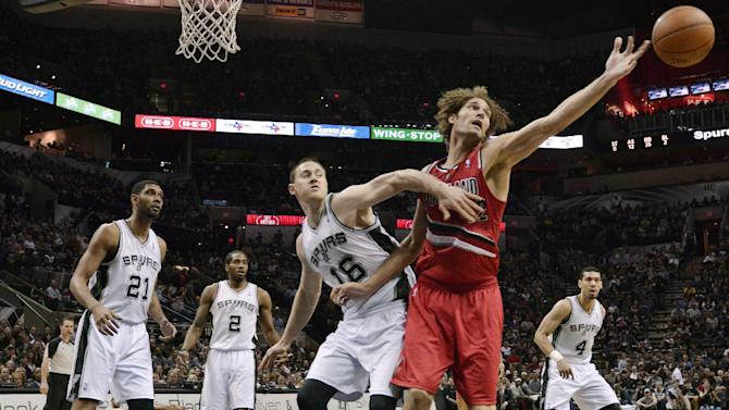 Portland Trail Blazers center Robin Lopez, right, and San Antonio Spurs forward Aron Baynes (16) watch a loose ball during the second half of an NBA basketball game Wednesday, March 12, 2014, in San Antonio. San Antonio won 103-90