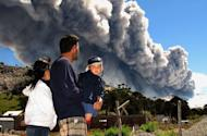 A family watches the Copahue volcano spewing ash from Caviahue, Argentina, some 1500 kms southwest of Buenos Aires on December 22, 2012. Southern Chile's Copahue Volcano belched plumes of ash skyward Saturday, prompting authorities there and in neighboring Argentina to issue a low-level alert