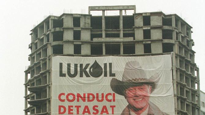 "FILE - In this Thursday Nov. 18, 1999 file photo, people cross the street in downtown Bucharest, Romania near an unfinished apartment building draped with a poster of U.S. actor Larry Hagman as J.R. Ewing from the television show ""Dallas."" The poster is part of a high-profile advertising campaign for the Russian oil giant Lukoil. ""Dallas"" was one of the few American TV series the late communist dictator Nicolae Ceausescu allowed to be shown on Romanian television.  Actor Larry Hagman, who for more than a decade played villainous patriarch JR Ewing in the TV soap Dallas, has died at the age of 81, his family said Saturday Nov. 24, 2012.  (AP Photo/Vadim Ghirda)"