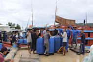 In this photo taken Wednesday, June 10, 2015 and released by the Government of the Republic of Palau, Vietnamese fishermen gather near their fishing ships anchored at the Marine Law Enforcement Division Port in Koror, Palau after being caught fishing illegally in the waters of the country. The tiny Pacific nation of Palau, fighting a rising tide of illegal fishing in its waters, has set fire to four boats of Vietnamese caught poaching sea cucumbers and other marine life in its waters. Palau's president, Tommy Remengesau Jr., said the boats were burned Friday morning, June 12, 2015. He hopes to turn most of the island nation's territorial waters into a national marine sanctuary, banning commercial fishing and exports apart from limited areas to be used by domestic fishermen and tourists. (The Government of the Republic of Palau via AP)