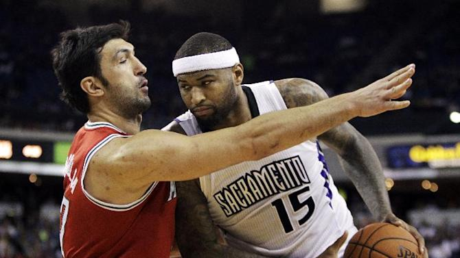Sacramento Kings center DeMarcus Cousins, right, protects the ball from Milwaukee Bucks center Zaza Pachulia, of Georgia, during the third quarter of an NBA basketball game in Sacramento, Calif., Sunday, March 23, 2014.  The Kings won 124-107