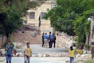 """An image released by the Syrian opposition's Shaam News Network shows Syrian children walking by as UN monitors speak to Syrian government soldiers as they visit the town of Kfra Nubul. Russia condemned as counterproductive a harsher diplomatic tone against the Syrian government on Wednesday, as the opposition accused Moscow of encouraging """"savage crimes"""" in the country"""