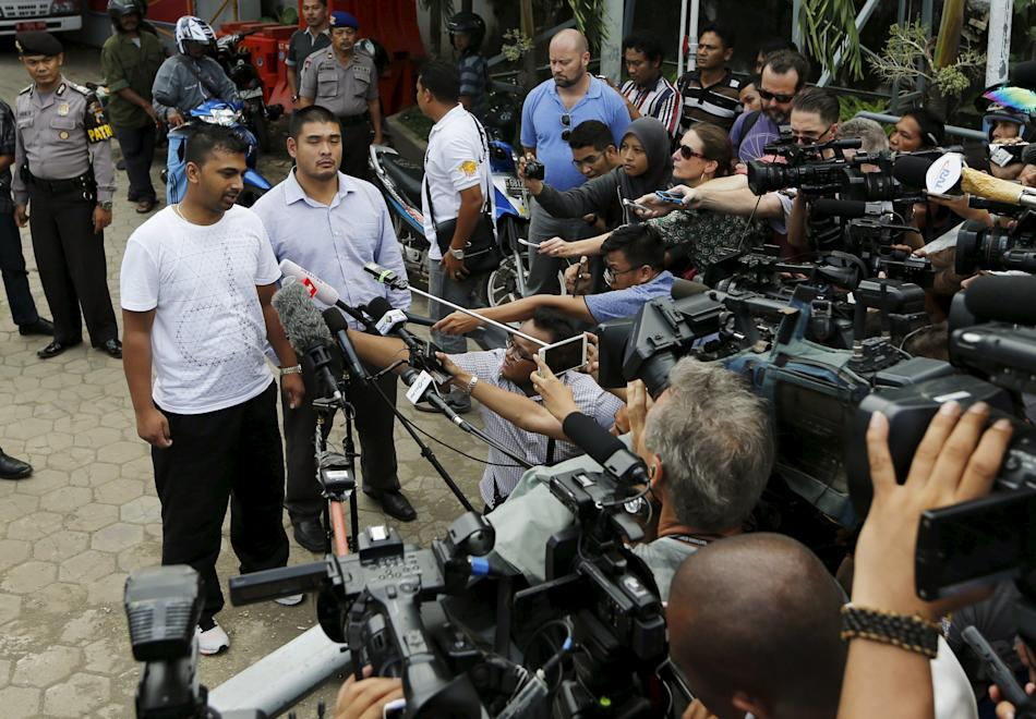 Chintu Sukumaran, brother of Myuran Sukumaran, talks to reporters while standing next to Michael Chan, brother of Andrew Chan, in Cilacap
