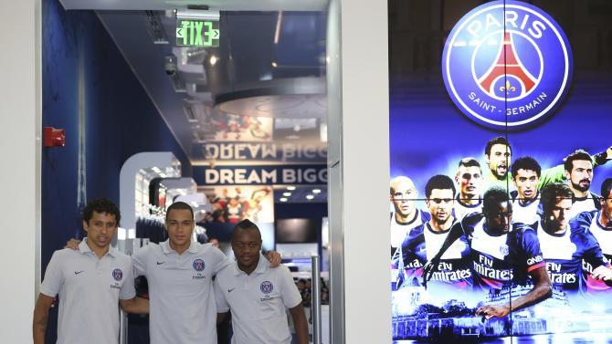 Paris Saint-Germain's Marquinhos, Gregory van der Wiel and Hervin Ongenda attend the official opening of the PSG store at Villagio Mall in Doha