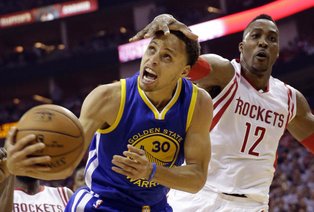 Dwight Howard (12), de los Rockets de Houston, comete falta a Stephen Curry (30), de los Warriors de Golden State, en la primera mitad del tercer juego de la final de la Conferencia Oeste de la NBA, e