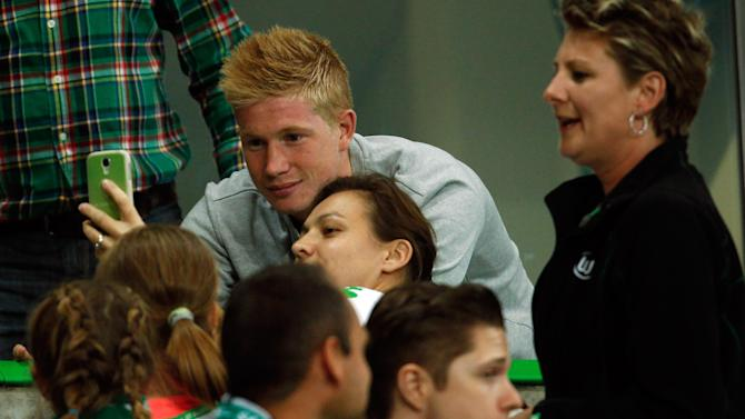 Supporters take pictures together with Wolfsburg's De Bruyne during the Bundesliga first division soccer match against Schalke 04 in Wolfsburg