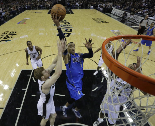 Dallas Mavericks' Monta Ellis (11) drives to the basket between San Antonio Spurs' Matt Bonner, left, and Tim Duncan, right, during the first quarter of Game 1 of the opening-round NBA basketb