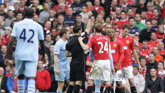 Manchester United's Jonny Evans, right, is sent off by referee Mark Clattenburg for a tackle on Manchester City's Mario Balotelli in their English Premier League soccer match at Old Trafford Stadium, Manchester, England, Sunday Oct. 23, 2011. (AP Photo/Jon Super)