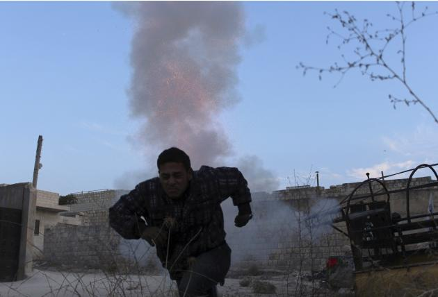 A Free Syrian Army fighter runs to take cover after firing a homemade mortar in Idlib