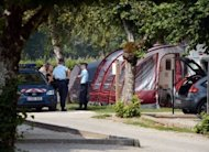 French police talk with investigators near the caravan of the British family killed on September 6 in the Alpine village of Saint-Jorioz. Investigators into the murders were pinning their hopes Friday on the seven-year-old girl wounded in the attack, as their probe appeared to make little headway
